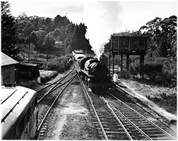 c.1960,loco SAR 701 with an up Bridgewater passenger crossing loco 930 on freight - overhead water tank,Aldgate