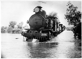 loco SAR T206 + another on goods train crossing flooded river - possible Central Australian Railway